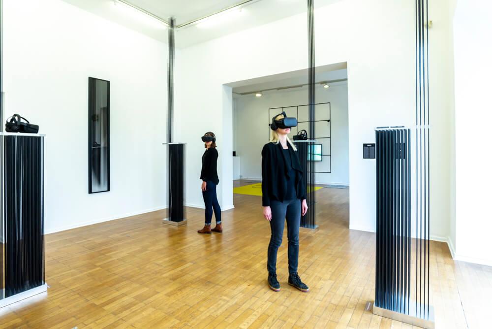 Zwei weiblich gelesene Personen mit VR-Brillen stehen in einem Ausstellungsraum, in dem ebenfalls Installationen aufgebaut sind.