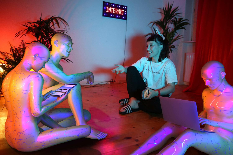 """Eine weiblich gelesene Person sitzt mit drei Bots auf dem Boden eines Zimmers und unterhält sich mit ihnen. Sie nutzen elektronische Geräte wie Laptops, Tablets und Smartphones. An der Wand prangt der Schriftzug """"Internet"""""""