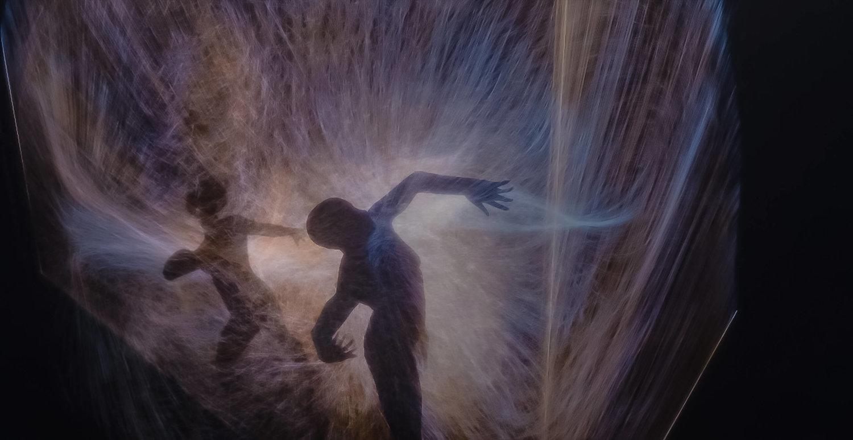 In einem schwarzen Raum bewegen sich zwei Körper wie in einem Tanz und werden von bunten Strahlen umgeben.