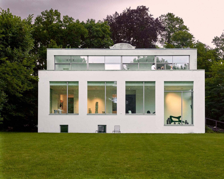 Blick auf ein modernes, weißes Gebäude von einer grünen Wiese aus. Durch die Fenster sind einige Keramikarbeiten leicht zu sehen. Oben auf der Terrasse des Hauses stehen Personen. Im Hintergrund sind Bäume zu sehen und der Himmel ist leicht rosa gefärbt.