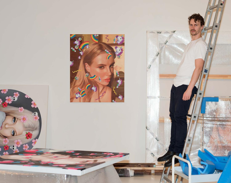 Der Maler Chris Drange steht an eine Alu-Leiter gelehnt am rechten Bildrand. Drei Malereien sind außerdem zu sehen, eine hängt an der Wand, eine lehnt daran, eine weitere liegt auf einem Tisch.