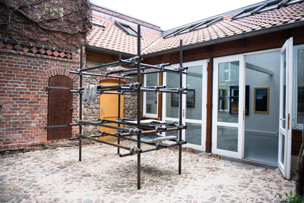 """Im Hof der Galerie Bernau steht ein Baugerüst, auf dem """"Textilien"""" aus Beton drapiert sind, eine Arbeit von Alison Darby."""