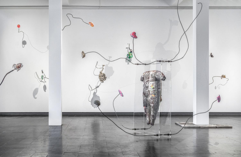 In bühnenhafter Präsentation steht inmitten fragiler Objekte ein kostümartiges Körperkonstrukt.