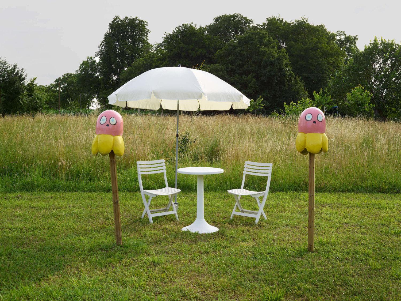 Zu sehen ist eine Gartenskulptur auf einer grünen Wiese, im Hintergrund ein Feld und Bäume zu sehen: Ein weißes Tisch, umgeben von zwei weißen Stühlen und einem weißen Sonnenschirm. Davor stehen links und recht zwei Pfeiler, denen witzige blumenartige Wesen mit Gesichtern aufgesetzt sind.