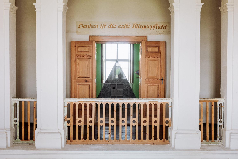 """Blick in einen Raum im Schloss Kummerow. Durch die geöffnete Flügeltür aus Holz zu erkennen: skulpturale Arbeiten von Henrike Naumann. Über der Tür steht in altmodischer Schreibschrift: """"Denken ist die erste Bürgerpflicht""""."""