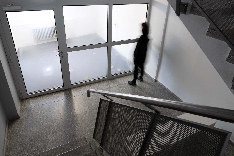 Zu sehen ist ein Treppenhaus, eine leicht verschwommene Person steht vor einer Fensterfront im Treppenhaus, Fenster und die Glastür der Front sind leicht beschlagen, dahinter liegt einer leerer, weißer Raum