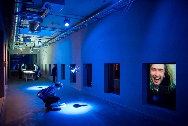 Ausstellungsansicht in der Betonhalle des silent green, der Raum ist blau erleuchtet, im Vordergrund hockt eine Besucherin über dem Boden und schaut etwas an, im Hintergrund stehen Menschen an einem Tisch, durch Fensteröffnungen ist ein Videostill zu erkennen