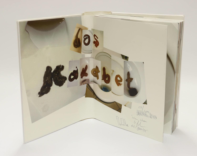 """Ein aufgeklapptes, aufgestelltes Buch, Es sind Bilder von Buchstaben eingeklebt, die aus Fäkalien gelegt wurden und zusammen """"das Kakabet"""" ergeben"""
