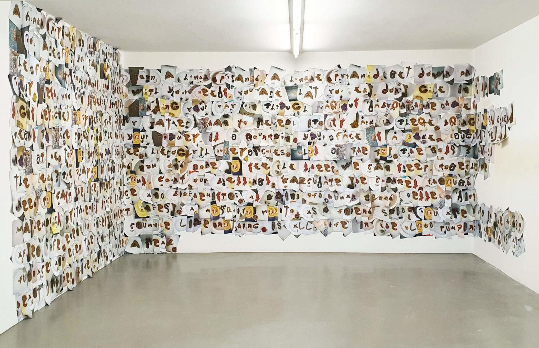 Ausstellungswand an der ganz viele Fotos von Buchstaben hängen, die aus Fäkalien gelegt wurden, zusammen ergeben sie einen vollständigen Text