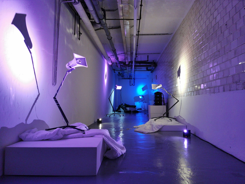 Installation von Rebekka Benzenberg mit mehreren Lautsprechern, die auf Gestellen auf Decken drapiert sind, angestrahlt in violettem und blauen Licht.