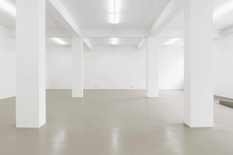 Ein leerer weißer Ausstellungsraum ist zu sehen mit vier Pfeilern im Raum, geradezu an der Wand befindet sich leicht oberhalb des Fußbodens zwei kleine schwarze Löcher aus denen ein Duft hinausströmt