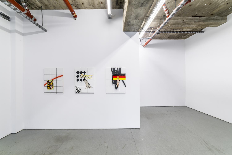Drei Leinwände mit Karomuster und Schäferhund- und Deutschlandflaggen-Motiven hängen in der Berliner Galerie Irrgang.