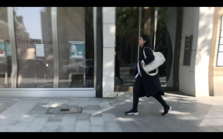 Eine schwarz gekleidete Frau mit weißer Sporttasche läuft durch eine Einkaufsstraße, sie passiert ein Ladengeschäft von Tiffany & Co.