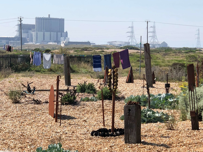 Ein Blick in einen garten, der mit Steinen ausgelegt ist und in dem Skulpturen stehen. Im Hintergrund hängt Wäsche an der Leine und es ist ein Atomkraftwerk zu sehen. Der Himmel ist blau.