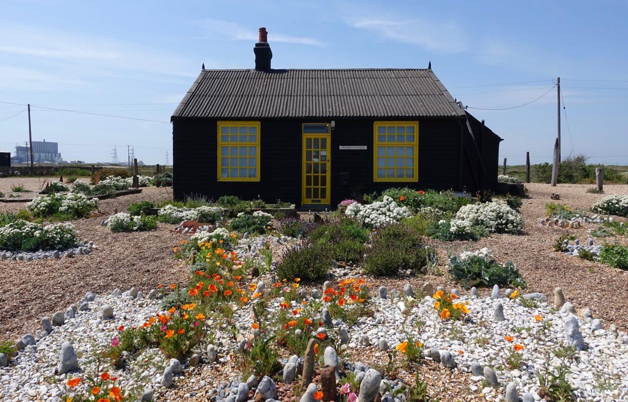 Man sieht ein schwarzes Haus mit gelben Fenster- und Türrahmen, davor ist ein blühender Garten und es liegen viele Steine aus, im Hintergrund ist in der Ferne ein Kernkraftwerk zu sehen, der Himmel ist blau