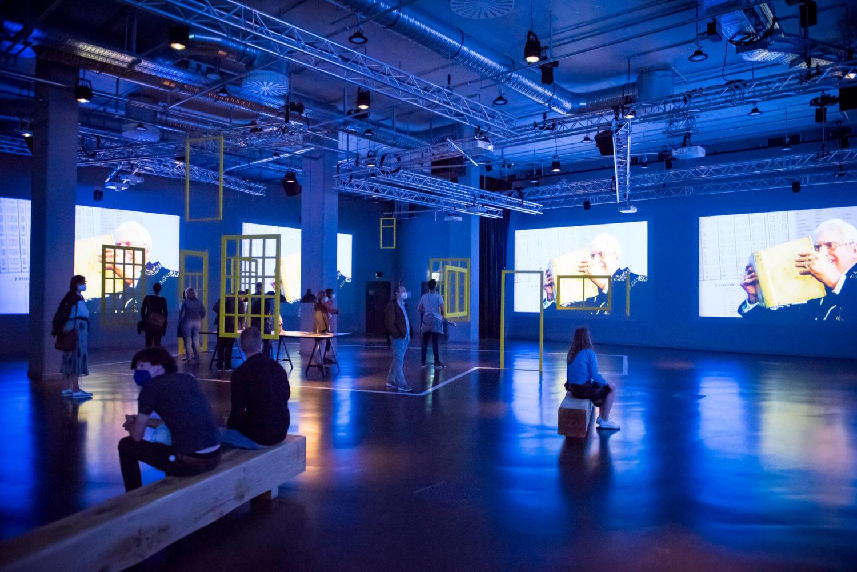 Ausstellungsansicht in der Betonhalle des silent green, der Raum ist blau erleuchtet und man sieht mehrere Videoprojektionen und Menschen, die auf Bänken davor sitzen. In der Mitte ist eine Rauminstallation mit schwebenden gelben Fenstern, die von der Decke hängen. Dazwischen ein Tisch, auf dem Fotos liegen