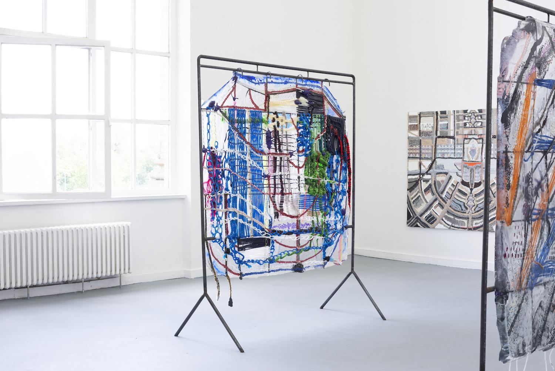 Auf zwei Metallgestellen sind Textil und Kordeln gespannt. An der Wand ein abstraktes Bild aus Acryl-Nägeln.