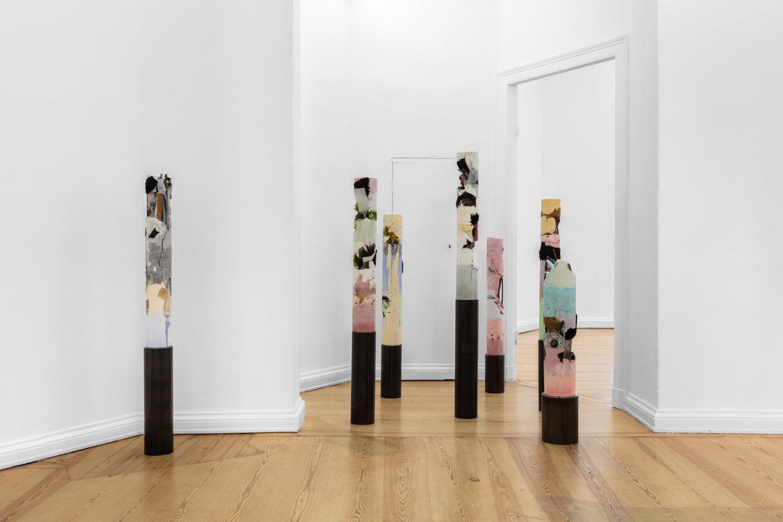 Ausstellungsansicht mehrerer Stelen von Sophie Erlund, die in bunten Pastellfarben leuchten und Bodenproben ähneln.