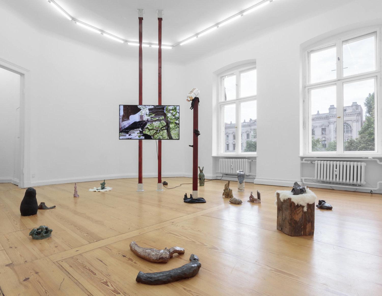 Ausstellungsansicht von Sophie Erlunds Ausstellung bei PSM. Mehrere Keramikobjekte sind im Raum verteilt, zentral ist eine Videoinstallation zu sehen.