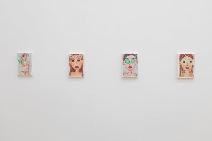 Ausstellungsansicht mehrerer kleinformatiger Gemälde, die Frauen mit Blumen oder Gurkenmaske zeigen.