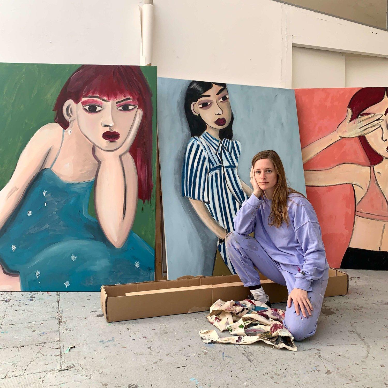 Das Foto zeigt Tatiana Defraine in ihrem Studio vor drei großformatigen Gemälden, die Frauen zeigen.