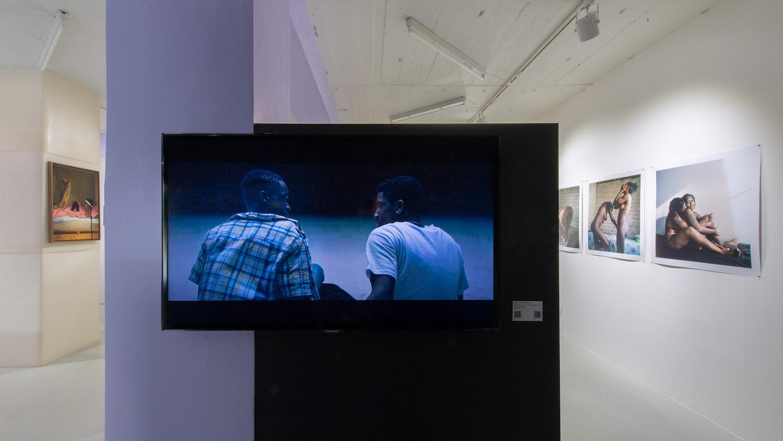Eine Videoarbeit mit zwei Schwarzen personen sowie fotografien von Schwarzen Personen im Schwulen Museum Berlin.