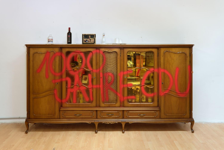 """Ein Holzschrank, auf den """"1000 Jahre CDU"""" in roter Farbe gesprüht ist."""