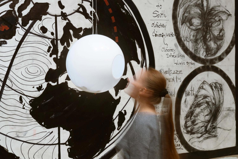 Eine verschwomme Person vor einer großen Wandarbeit, eine weiße Kugel mit einem Loch hängt von der Decke
