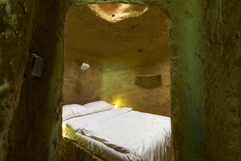 """Lehmverkleideter Innenraum der Skulptur """"Boob Hills"""" von Laure Prouvost. Man sieht ein Bett mit weißer Bettwäsche, eine Lampe an der Wand und durch das Loch in der Decke fällt licht."""