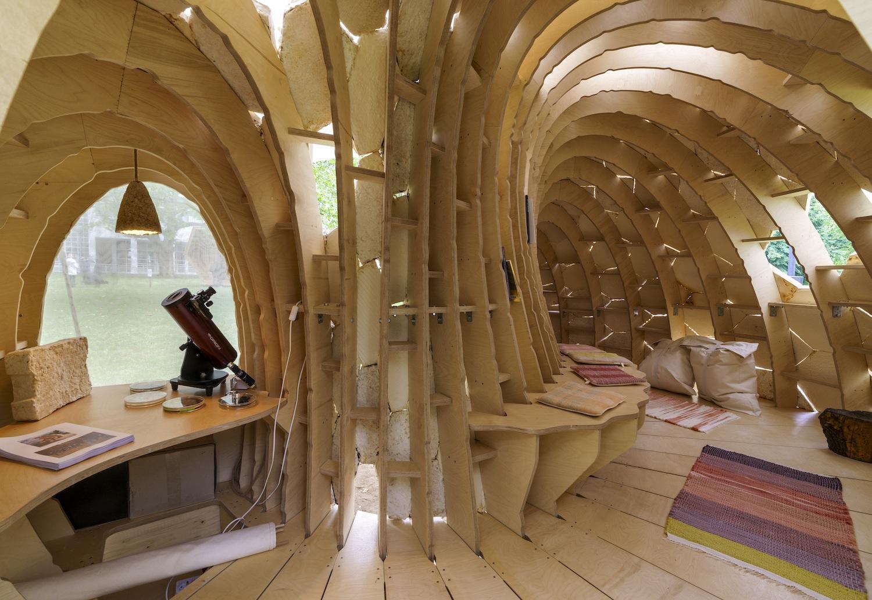 """Der Innenraum des """"MY-CO-SPACE"""" ist aus einer Art Holzgerippe geformt. Darin: Teppiche, Kissen, ein Mikroskop, darüber eine Lampe."""
