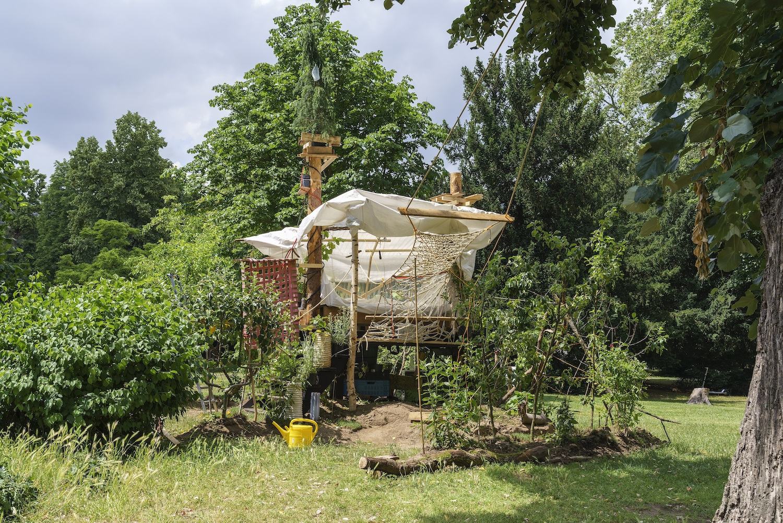 Baumhaus von Terence Koh inmitten von Bäumen. Zu Füßen des Hauses eine Art improvisierter Garten.