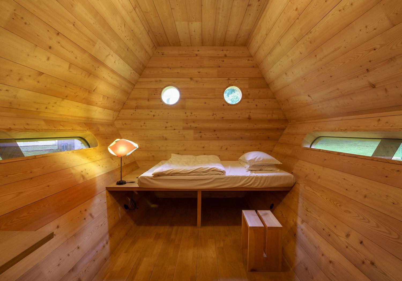Holzverkleideter Innenraum der Schütte-Hütte mit einem Bett, einem Hocker und einer Lampe.