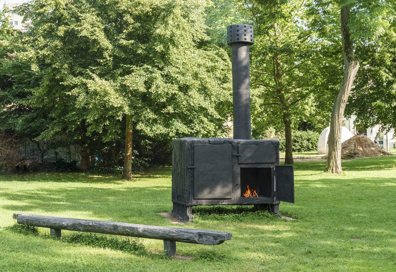 Im Metzlerpark steht ein großer schwarzer Ofen von Sterling Ruby. Darin lodern Flammen, davor steht eine Holzbank.