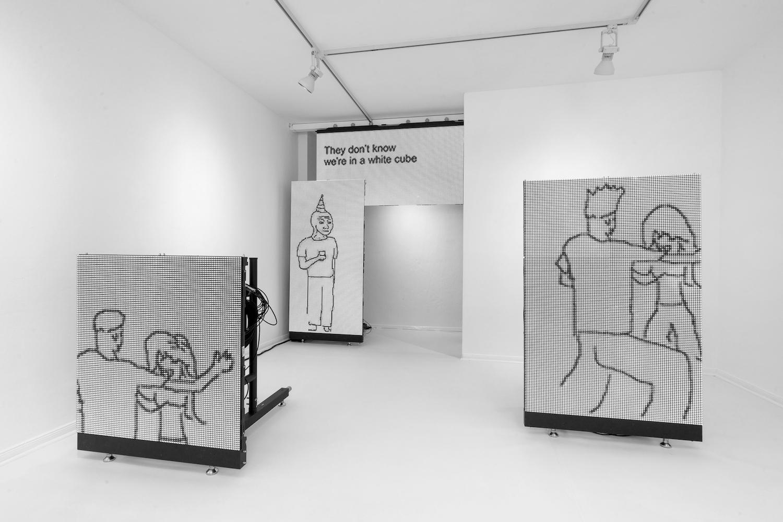 """Mehrere Screens in einem White Cube zeigen Fragmente eines """"They-Don't Know""""-Memes."""