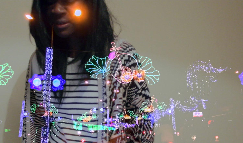 Person mit langen Haaren vor einer grau-weißen Wand, im Vordergrund sind in bunten Farben leuchtende Symbole und Elemente zu sehen, die sich durch das Bild zu bewegen scheinen