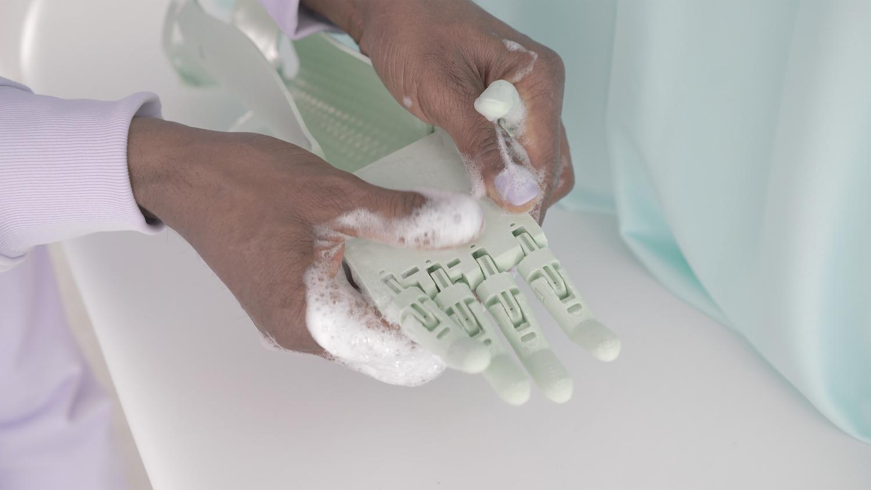 Fliederfarben lackierte Männerhände waschen eine hellgrüne Roboterhand.