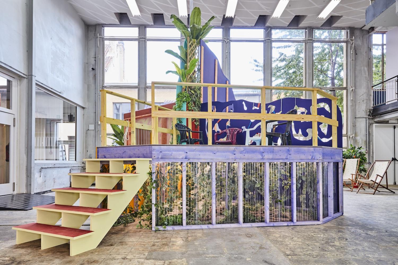 Bunte Installation von Sol Calero in Betonhalle mit hohe Decke und großen Fenstern.