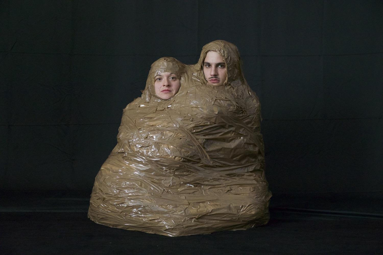 Sophia Süßmilch und Valentin Wagner aka Spatzi Spezial komplett eingewickelt in Klebeband, kauernd, nur die Gesichter sind frei.