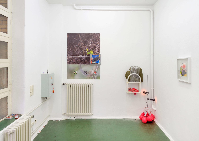 Kleiner Ausstellungsraum mit weißen Wänden und grünem Boden, links sind zwei Heizkörper zu sehen, eine Installation mit rotem Licht rechts unten in der Ecke, geradezu über einer Heizung hängt ein beklebter Fotodruck und ein kleines gerahmtes Bild