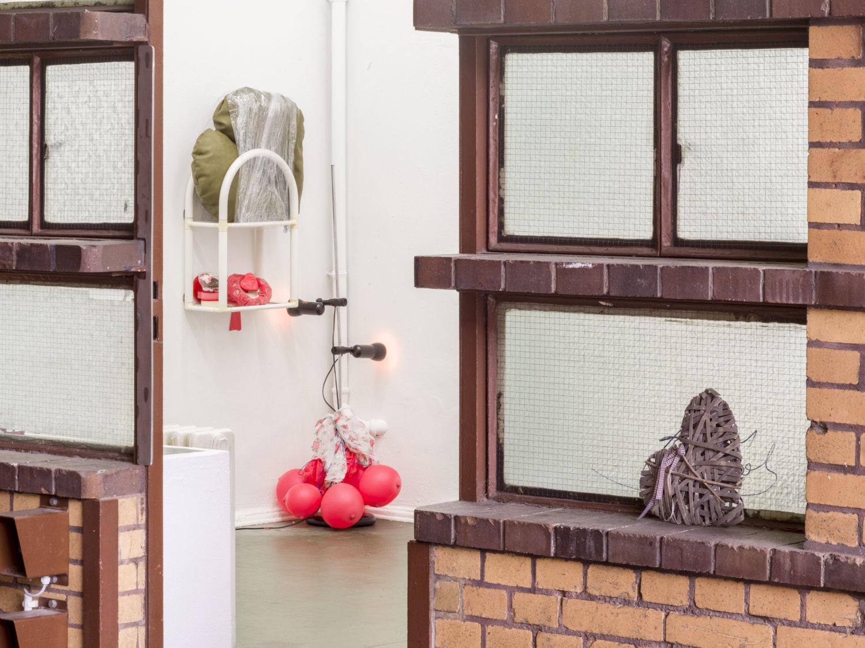 Blick hinein in den Ausstellungsraum von Grzegorzki Shows, im Vordergrund sind Fenster und ein Herz zu sehen, durch die Tür blickt man in die Ecke und sieht eine Installation mit rotem Licht und Herzen, ein Herz-Kissen ist in Frischhaltefolie eingewickelt