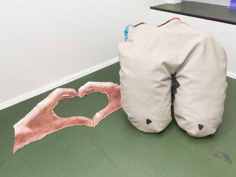 Grüner Ausstellungsbode, links ist eine Art Teppich zu sehen mit zwei Händen, die zusammen ein Herz bilden, rechts daneben eine Art Sitzsacke, der aussieht wie zwei herunterhängende Brüste mit Herzchen drauf