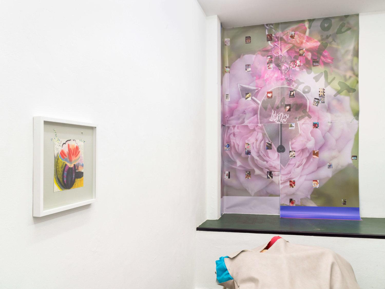 Ausstellungsansicht: links ein kleines gerahmtes Bild zu sehen, geradezu an der Wand hängt ein großer Druck, der mit kleinen Bildern beklebt ist, der Druck zeigt eine große Rose