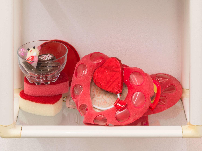 Detailansicht aus einer Installation: zu sehen sind zahlreiche Dinge, die eine Herzenform haben, z.B. Schokolade oder ein Lolli