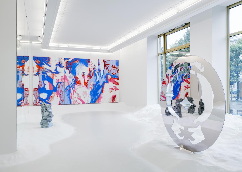 In der Galerie Peres Projects liegt weißer Sand. Im Raum: eine reflektierende Metallskulptur, eine kleine hellblaue Skulptur und an der Wand ein abstraktes Gemälde.