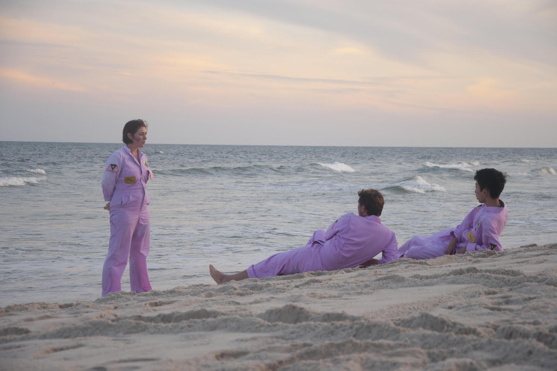 Drei Personen in rosafarbenen Overalls am Strand vor untergehender Sonne. Zwei liegen mit Blick aufs Wasser, eine blickt stehend auf sie herab.