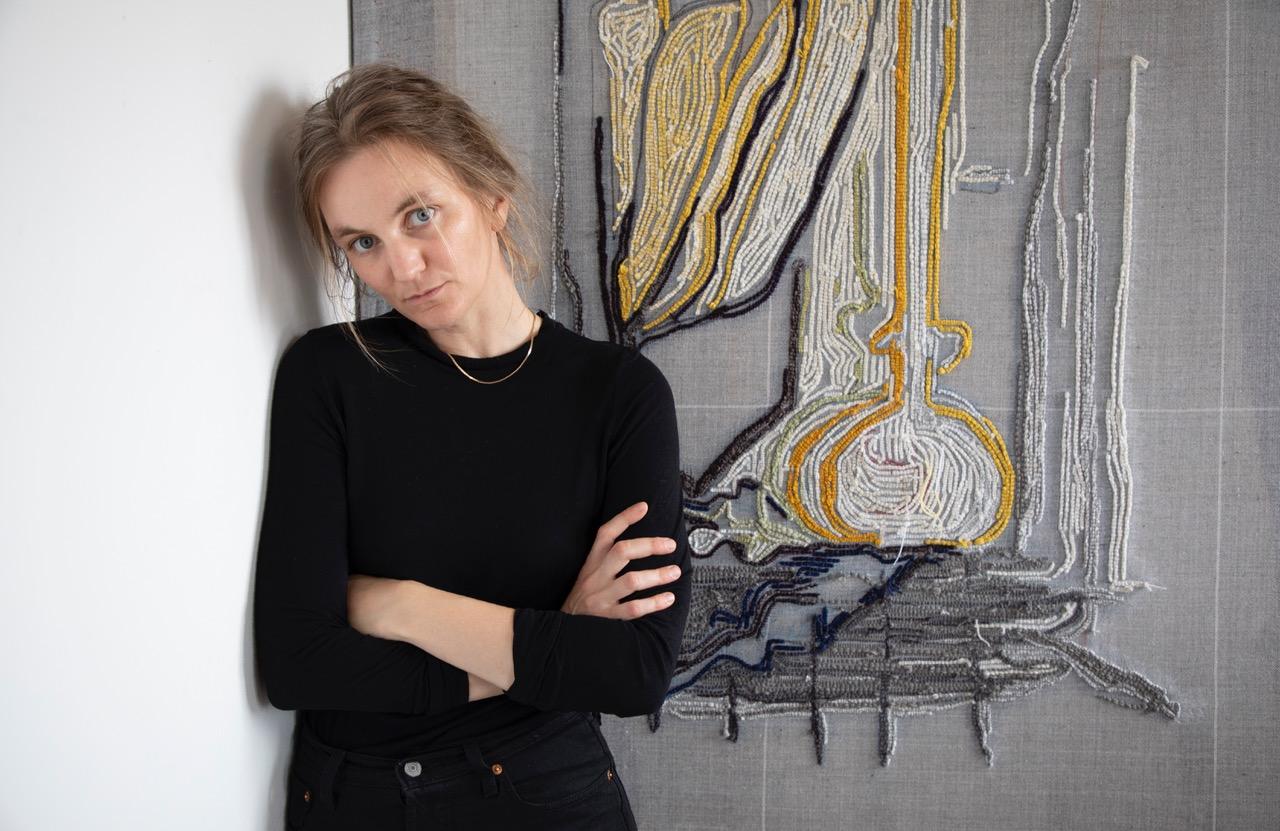 Die Künstlerin Pia Ferm posiert mit verschränkten Armen vor einer noch unfertigen Textilarbeit in ihrem Atelier.