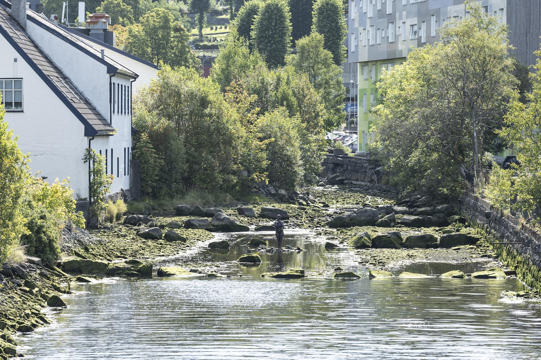 Blick ins Flussbett, im Wasser steht eine Bronzeskulptur von Bea Schlingelhoff: eine Frau hält ein Baby im Arm.