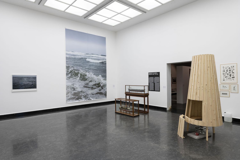 Verschiedene Arbeiten, darunter eine Meeresfotografie von Wolfgang Tilmans und alte Bootsmodelle, installiert in der Bergen Kunsthall.