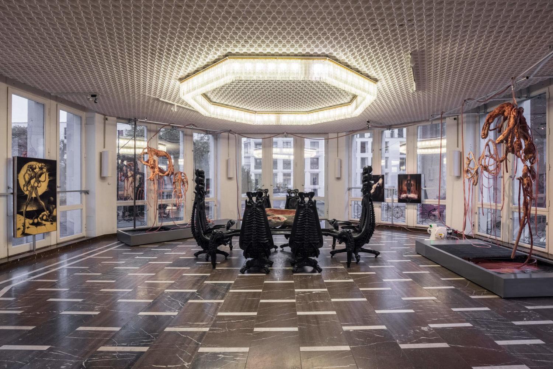 In der Mitte eines oktogonalen Raumes steht ein Tisch mit von HR Giger entworfenen Stühlen. Darum herum sind skulpturale Arbeiten von Mire Lee zu sehen, aus denen Flüssigkeiten austreten.