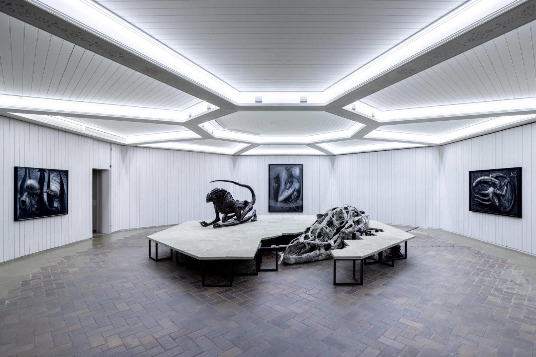 In einem oktogonalen Raum steht ein Podest in der Raummitte. Darauf sind Arbeiten von HR Giger und Mire Lee zu sehen. An den Wänden hängen Zeichnungen des Künstlers, die allesamt alienartige Kreaturen zeigen.